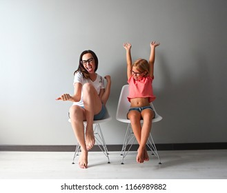 Happy mother and her little daughter sitting on the chairs by the grey wall. Portrait of mother and daughter with eyeglasses