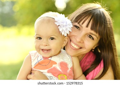 Happy mother with her little daughter in summer park
