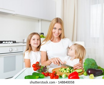 Happy mother and her little daughters cutting vegetables in the kitchen