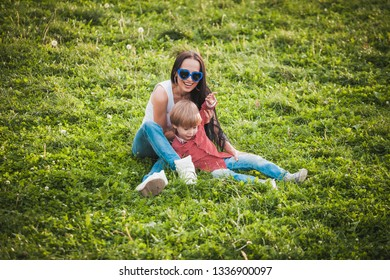 happy mother with her little son sitting on grass in summer day and smiling