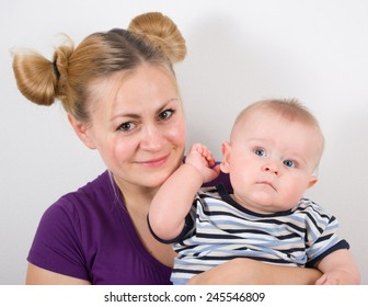 Happy mother with her little son on a grey background