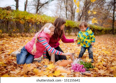 happy mother with her son and daughter drinking tea in the autumn meadow