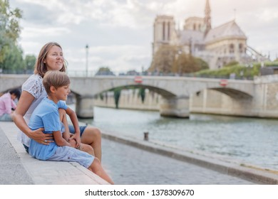 Happy mother and her son having fun near Notre-Dame cathedral in Paris, France. Tourists enjoying their vacation in France. Traveling family concept