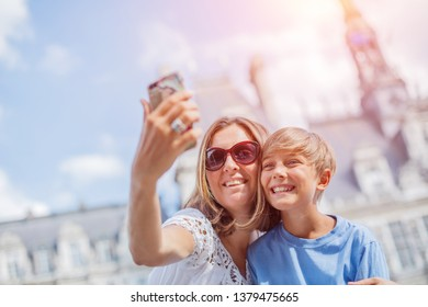 Happy mother and her son making selfie near Hotel de Ville in Paris, France. Tourists enjoying their vacation in France. Traveling family concept