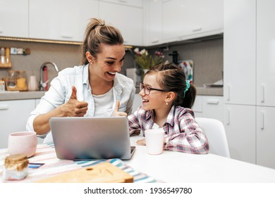 Happy mother with her young daughter enjoying in online shopping or working from home. Business from distance and virtual communication with family and friends.