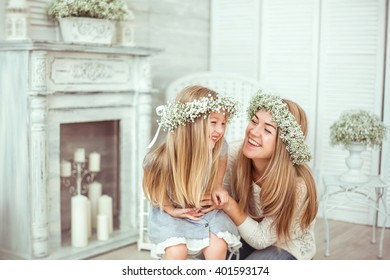 A happy mother and her young daughter are having fun. They are both laughing. They are having casual clothes and floral wreathes on. The atmosphere of happiness is all around them.