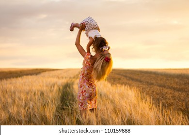 happy mother holding baby smiling on a wheat field in sunlight. outdoor shot