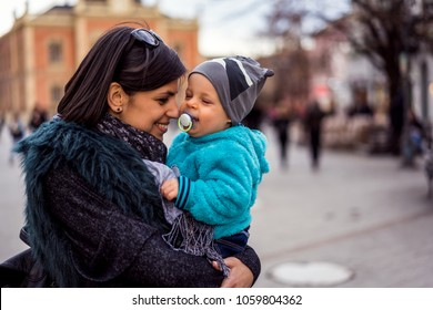 Happy mother holding cute child in the street