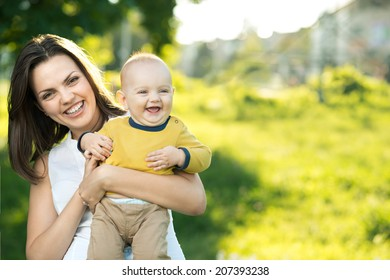 Happy mother holding a young son in the park