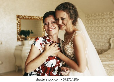 Happy mother holds bride's hand standing with her in the room