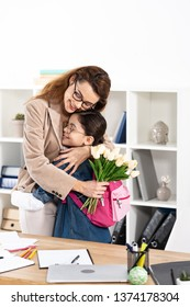 happy mother hugging cute daughter and holding flowers in office