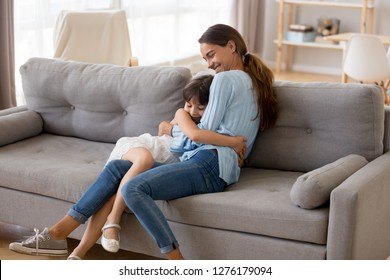 Happy mother hugging cute little girl sitting together on sofa in living room, smiling mom embracing kid, mum and daughter cuddle having fun at home, sincere warm relationships of mommy child concept