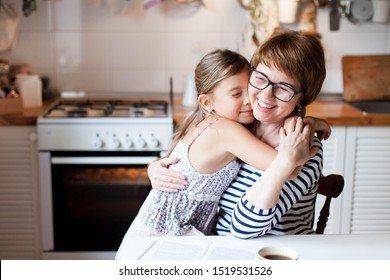 Happy mother is hugging daughter in cozy home kitchen. Woman and cute child girl are smiling. Family is using oven. Kid is enjoying kindness, embrace, care, support. Lifestyle authentic moment.