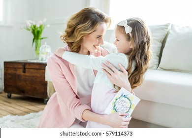 Happy mother hugging her adorable little daughter and holding greeting card for Mothers Day