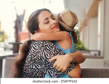 Happy mother hugging her daughter with love and natural emotion smiling with closed eyes