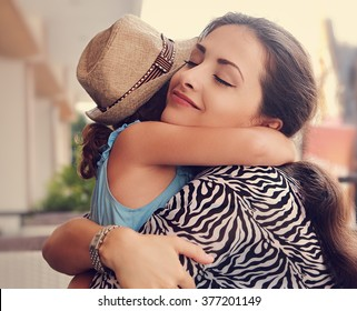 Happy mother hugging her daughter with love and natural emotion with closed eyes. Closeup toned portrait of family love