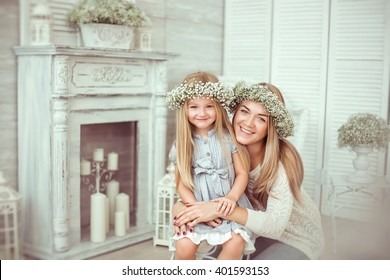 A happy mother is hugging tight her young daughter. They are looking straight and smiling. They are having casual clothes and floral wreathes on. The atmosphere of happiness is all around them.