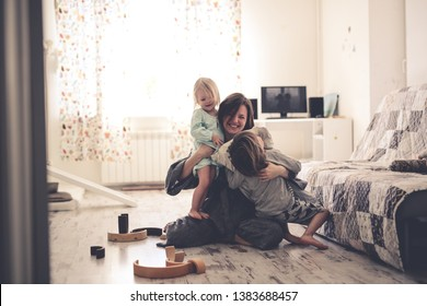 Happy mother hugs her children siblings on the floor in a real room, emotions and lifestyle in the bright interior, enjoying time together at home
