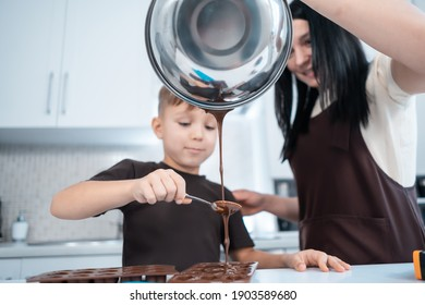 happy mother and kid making chocolate candies or sweets at home modern kitchen