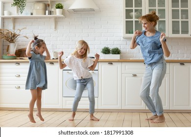 Happy mother and kids dancing and frolicking barefoot on wooden floor in cozy spacious kitchen. Young mom and preschool daughters in casual clothes spending time at home having fun together