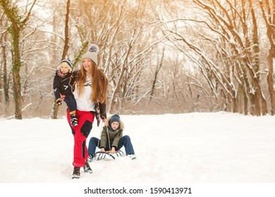 Happy mother and kids having fun with sledge in winter park. Family enjoying spending time together while riding on a sled. Family concept. Winter holidays