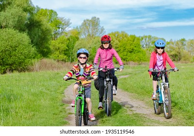 Happy mother and kids on bikes cycling outdoors in park, active family sport  and fitness together
