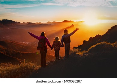 Happy mother with kids travel in sunset mountains