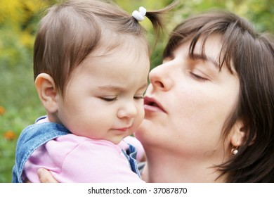 Happy mother kissing baby daughter outdoors