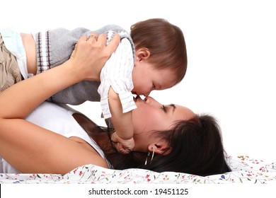 happy mother kissing her baby over white