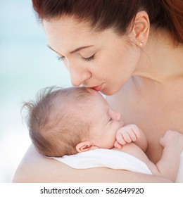 Happy mother kissing her cute sleeping baby. Motherhood and children concept. Happy family, mother and daughter portrait. Close up