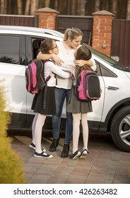 Happy mother kissing her two daughters after meeting them from school
