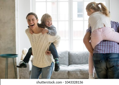 Happy mother laughing piggybacking little son playing with family at home, cheerful parents carrying kids on back having fun together, children boy and girl enjoying active game with mom and dad