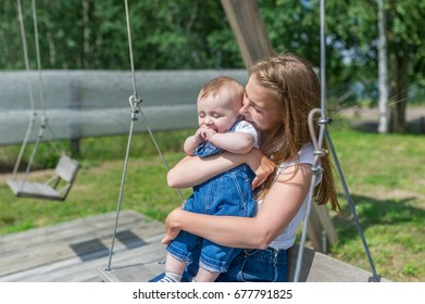 Happy mother and laughing son on swing in a park.