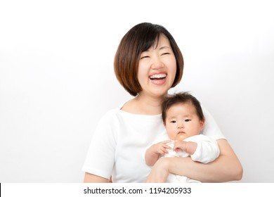 A happy mother laughing while holding a newborn baby. Newborn baby, love, childcare, parent and child, happy image