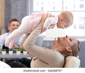 Happy mother lifting up high little baby daughter, having fun, laughing. Father watching from background.