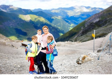Happy mother with little baby girl and two kids boys travelling in backpack.