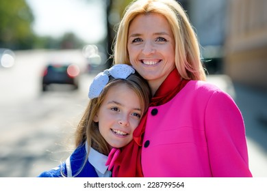 happy mother and little beautiful daughter having fun together in city