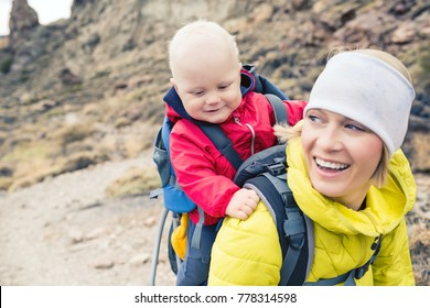 Happy mother with little boy travelling in backpack. Hiking adventure with child on autumn family trip in mountains. Vacations journey with infant carried on back, weekend travel in Tenerife, Spain.