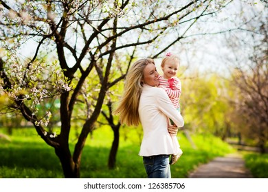 Happy mother and little child playing in a spring park