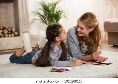 happy mother and little daughter drawing with colored pencils and smiling each other at home