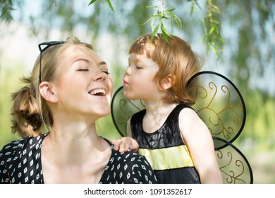 happy mother with little daughter dressed in costume bees walking in sunny park on nature in spring