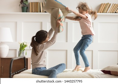 Happy mother and little daughter having fun, pillows fight, playing with cushions in bedroom, pretty preschool girl jumping on bed, funny family activity at home, enjoying weekend together
