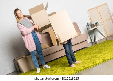 happy mother and little daughter holding cardboard boxes while moving home