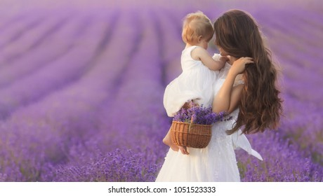 Happy mother with little daughter on lavender background. Beautiful woman and cute baby playing in meadow field. Family holiday in summer day.