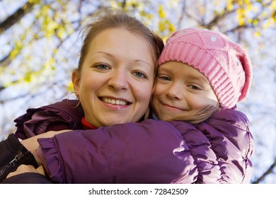 Happy mother with little daughter outdoor in autumn