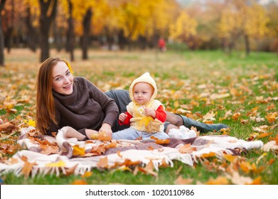 Happy mother and little daughter are playing in the autumn park.