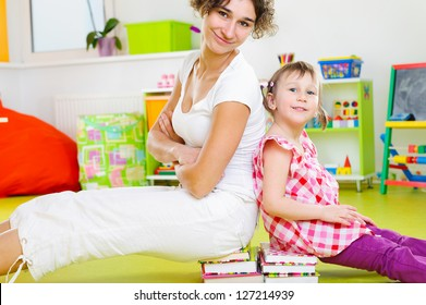 Happy mother and little daughter playing at home