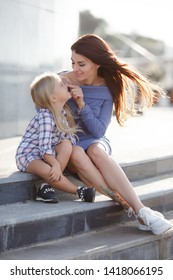 Happy mother and little daughter playing on the nature in city. Cute kid girl kissing her happy enjoying mother with closed eyes and natural emotion