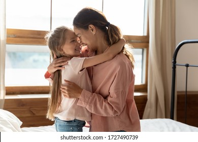 Happy mother and little daughter touching noses, expressing love and care, family enjoying tender moment, preschool girl and mum sitting on comfortable bed in bedroom, good trusted relationship