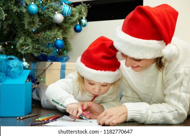 happy mother and little daughter writing a letter to Santa Claus near Christmas tree. New Year and xmas people